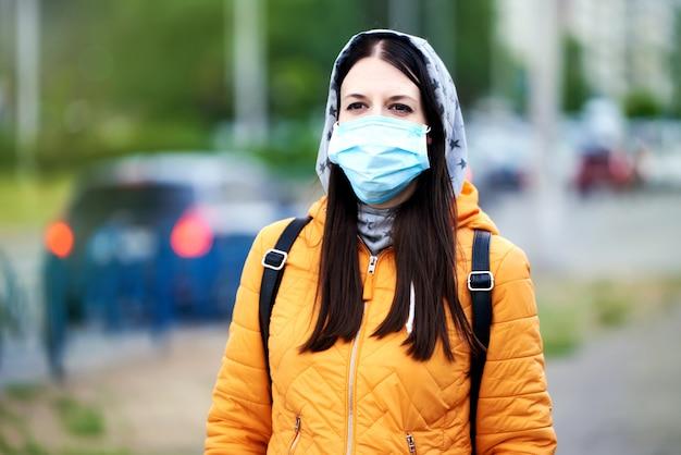 Uma garota em uma máscara médica, capuz e maleta, olhando para o futuro, no futuro. hey em uma jaqueta laranja
