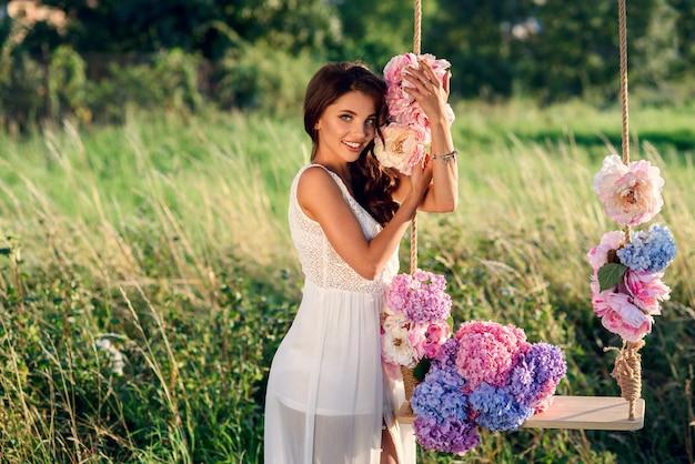 Uma garota encantadora com um sorriso perfeito em um vestido branco perto de balanço de madeira com um buquê de flores coloridas concurso ao pôr do sol.