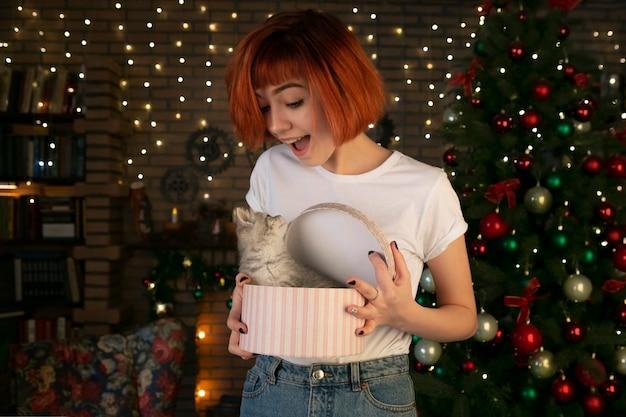 Uma garota encantadora de aparência caucasiana segura uma caixa com um gatinho nas mãos. presentes de natal.