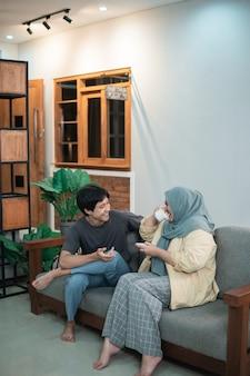 Uma garota encapuzada e um garoto asiático conversam depois do café na sala de estar sentados em uma cadeira de madeira