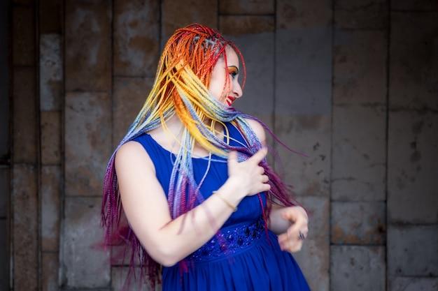 Uma garota engraçada com maquiagem brilhante e tranças coloridas em um vestido azul claro está girando e rindo alegremente nas ruas vazias da cidade da primavera