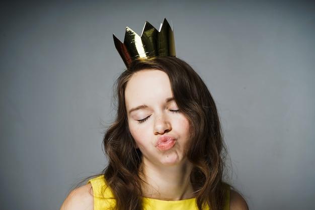 Uma garota engraçada com um vestido amarelo fez beicinho nos lábios, uma coroa de ouro na cabeça