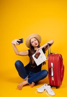 Uma garota engraçada de chapéu viaja de férias, com uma grande mala vermelha, faz uma selfie