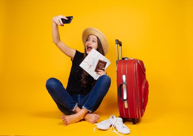 Uma garota engraçada vai viajar, fazendo selfies com ingressos, uma grande mala vermelha