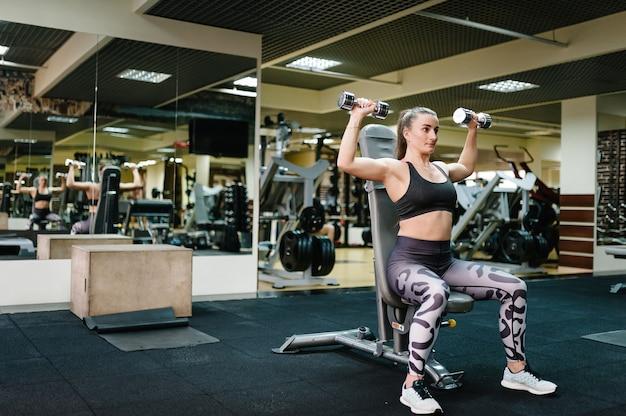 Uma garota envolvida em esportes e fitness com halteres perto de espelho no ginásio.