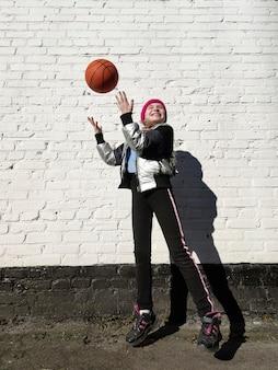 Uma garota esportiva brinca com uma bola de basquete perto de uma parede de tijolos brancos.