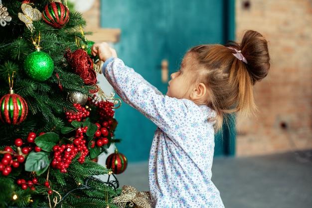 Uma garota está decorando uma árvore de natal em casa. o conceito de um feliz natal, férias, família.