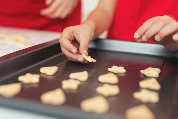 Uma garota está fazendo biscoitos em uma assadeira.