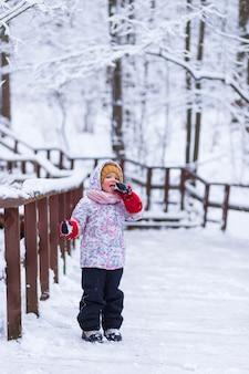 Uma garota está perto da grade na floresta de inverno