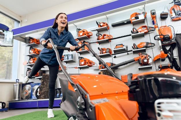 Uma garota está posando com um cortador de grama em uma loja de ferramentas.