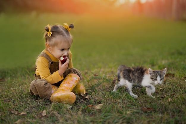 Uma garota está sentada na grama no jardim ao pôr do sol com um gatinho