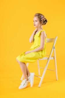 Uma garota está sentado em uma cadeira branca sobre um fundo amarelo.