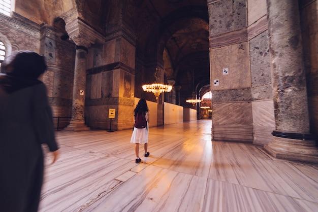 Uma garota examina o interior de hagia sophia, uma viagem de verão