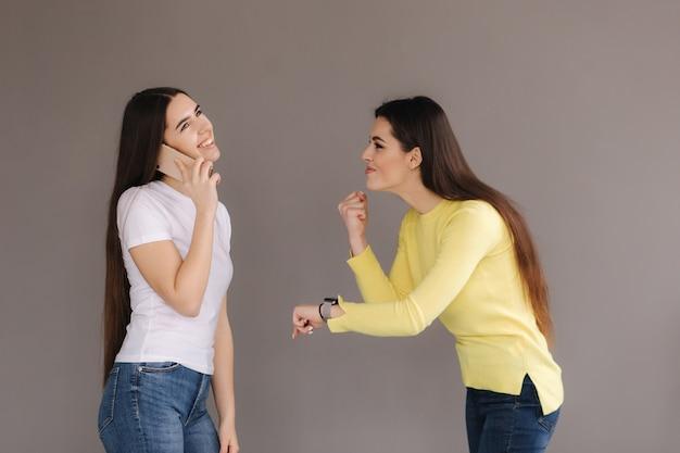 Uma garota fala por telefone e sorri para outra jovem atraente surpresa e zangada no estúdio em