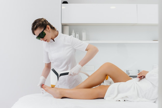 Uma garota faz depilação a laser em um equipamento moderno em um salão de spa