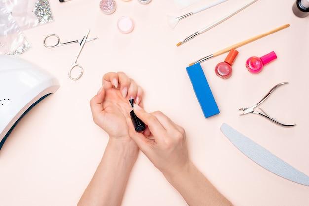 Uma garota fazendo as unhas em casa, close-up das mãos. a vista do topo