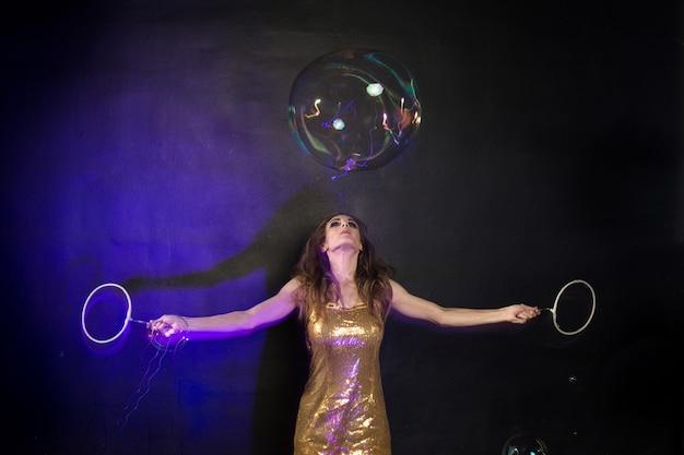 Uma garota fazendo grandes bolhas de sabão em um estúdio preto