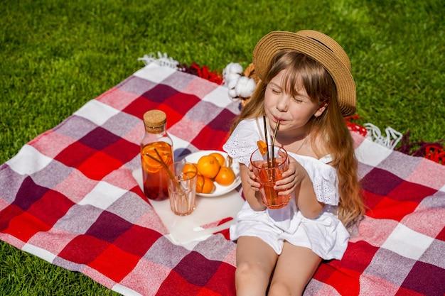 Uma garota fazendo piquenique na grama um cobertor xadrez vermelho uma cesta de vime uma bebida natural feita de laranjas ...