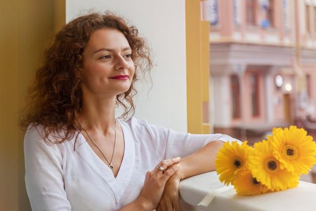 Uma garota feliz caminha pela cidade com um buquê de flores amarelas de gerber