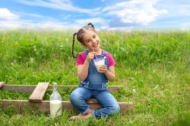 Uma garota feliz com tranças de macacão jeans e uma camiseta rosa segura um copo de leite com um canudo rosa, senta-se em uma escada de madeira, em um campo na grama. céu azul com nuvens. copie o espaço