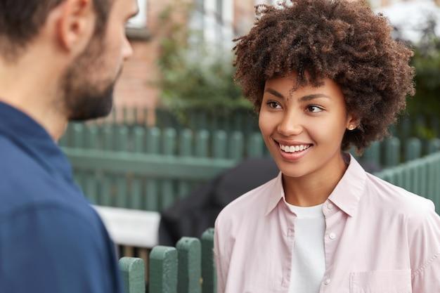 Uma garota feliz de pele escura conhece seu colega de grupo
