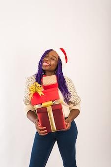 Uma garota feliz de pele escura tem muitos presentes vermelhos nas mãos.