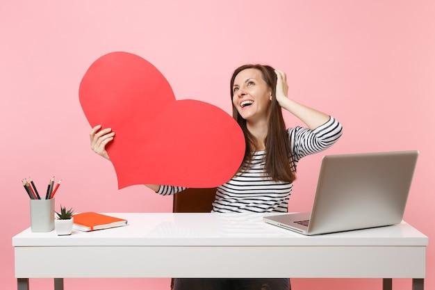 Uma garota feliz e sonhadora olhando para cima segurando um coração vermelho vazio em branco, sentar no trabalho na mesa branca com o laptop