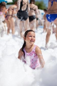 Uma garota feliz e sorridente em um maiô rosa brinca com espuma em uma festa da espuma em um parque aquático em um dia ensolarado