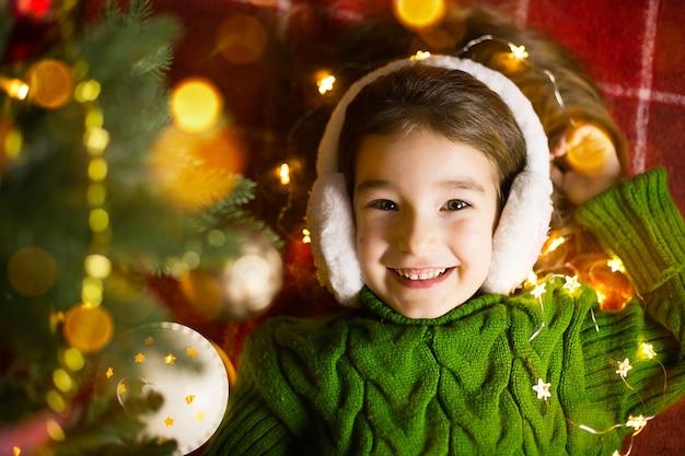 Uma garota feliz em fones de ouvido de pele encontra-se perto da árvore de natal em guirlandas e luzes em um suéter quente em um cobertor aconchegante. natal e ano novo, véspera de feriado, clima mágico