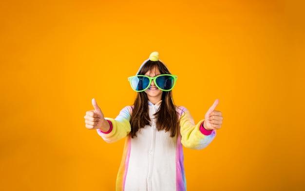 Uma garota feliz em um macacão de pelúcia mostra uma classe com as mãos em um fundo amarelo com um espaço para texto
