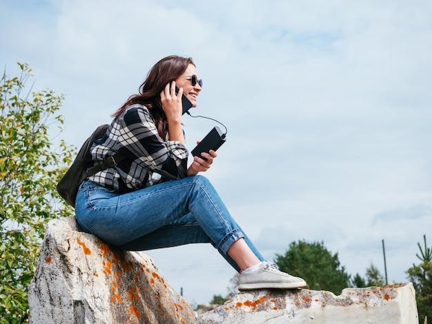 Uma garota feliz nas montanhas está rindo enquanto fala ao telefone carregando do banco de energia