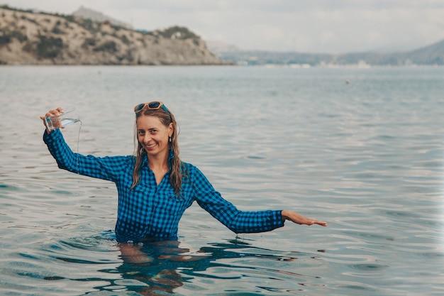 Uma garota feliz se senta no rio e bebe água de um copo. conceito de fontes naturais limpas, proteção ambiental