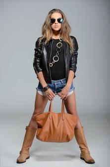 Uma garota fica em uma jaqueta de couro com um saco.