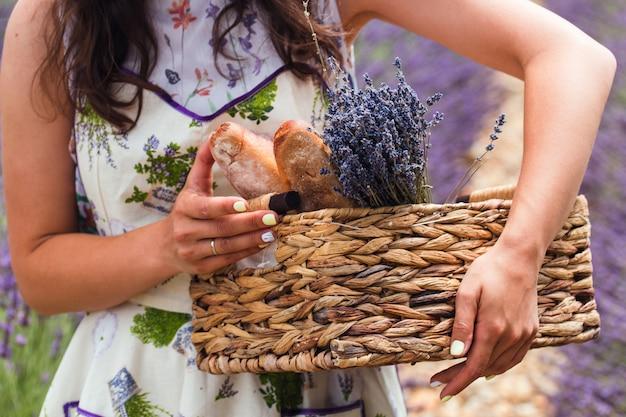 Uma garota fica no meio de um campo de lavanda, segurando nas mãos uma cesta