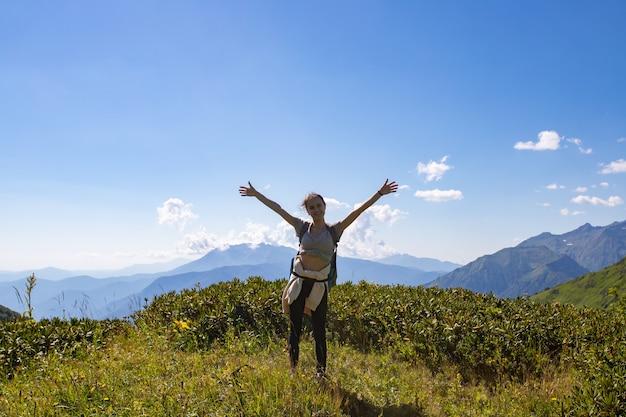 Uma garota fica no topo de uma montanha com as mãos para cima, liberdade, conceito de felicidade.
