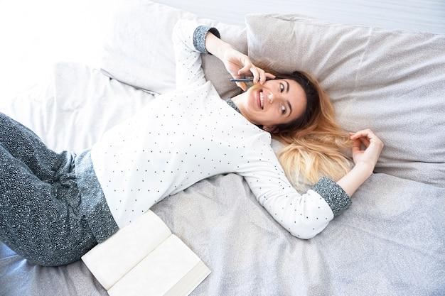 Uma garota ficando no quarto com pijama e ligando com um smartphone enquanto os livros são abertos em sua cama
