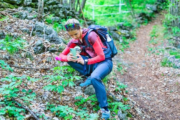 Uma garota fotografa flores com um smartphone durante uma viagem na colina