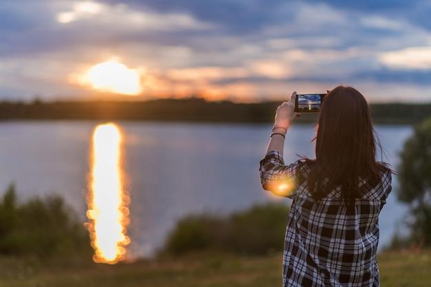 Uma garota fotografa o pôr do sol no lago ao telefone