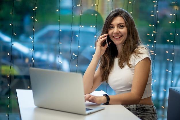Uma garota freelance sorridente, trabalhando em um laptop em um café e falando ao telefone, o dia de trabalho de uma jovem livre ou estudante.