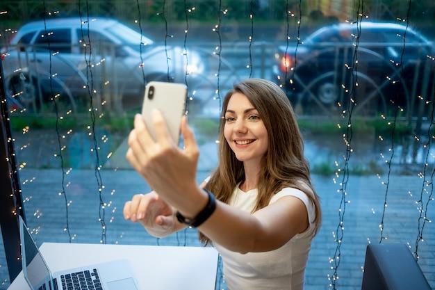 Uma garota freelancer sorridente tira uma selfie ao telefone ou faz uma videochamada, um dia de trabalho de uma jovem livre ou um aluno com um laptop.