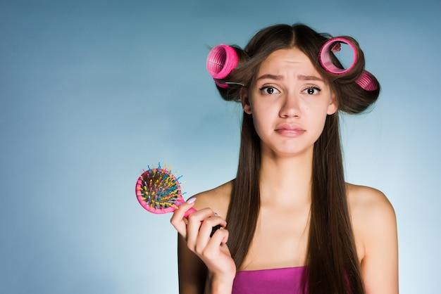 Uma garota frustrada com rolinhos na cabeça em um fundo azul