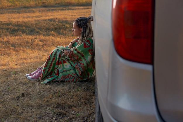 Uma garota hippie em um cobertor colorido e tênis rosa senta ao lado do carro no meio do campo o c ...