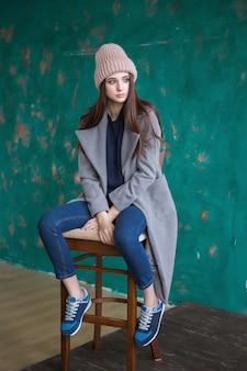 Uma garota hipster com longos cabelos castanhos, vestindo um casaco elegante e boné de malha está olhando para o lado em pé sobre um fundo de cerca de arte verde escuro em um estúdio. mock up horizontal.