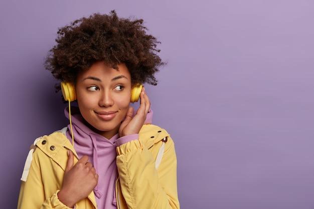 Uma garota hipster de pele muito escura ouve um audiolivro em fones de ouvido, focada ao lado com uma expressão sonhadora e usa roupas casuais