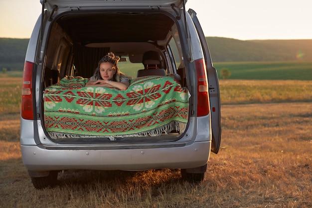 Uma garota hipster deita-se na cama em uma minivan contra o fundo do campo e o sol poente.
