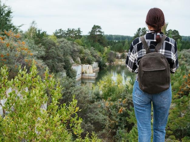 Uma garota hipster em roupas casuais confortáveis está parada em um penhasco com vista para o lago