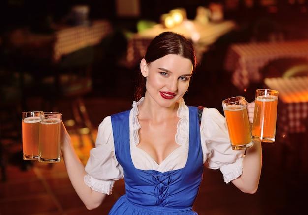 Uma garota jovem e atraente com roupas da baviera segura muitas canecas com cerveja no pub durante a celebração da oktobfest