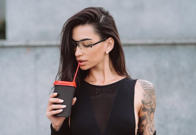 Uma garota jovem e atraente com tatuagem bebendo café de rua