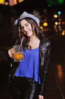 Uma garota jovem e atraente com um chapéu cinza da baviera bebe cerveja ou um coquetel de cerveja através de um canudo na superfície de um bar. oktoberfest, dia de são patrício