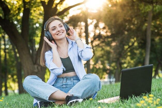 Uma garota jovem e atraente em fones de ouvido, sentado na grama do gramado. usando um laptop para ouvir música com fones de ouvido
